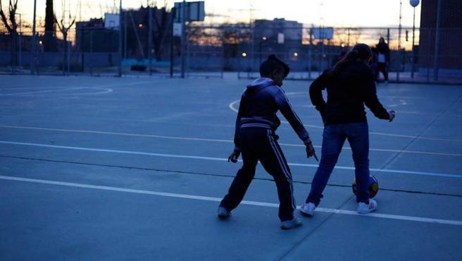 Dos niños juegan con una pelota en la calle.