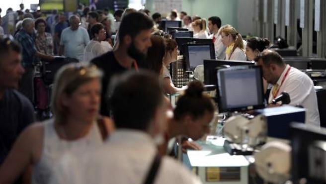 Personal de facturación de Vueling atiende a los viajeros en el Aeropuerto de El Prat que han sufrido retrasos y cancelaciones en sus vuelos de la aerolínea.