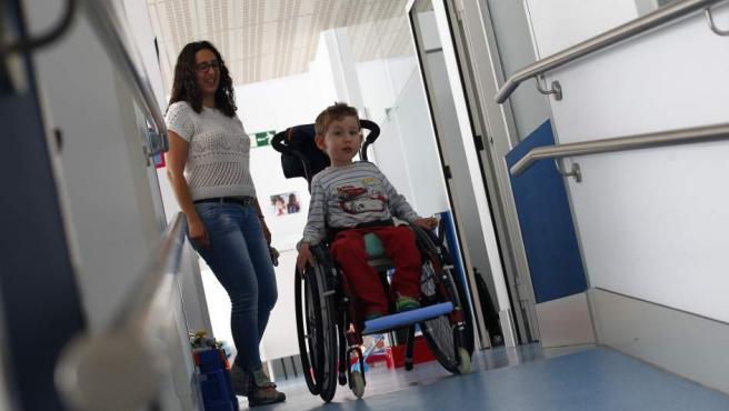 Álvaro, afectado por atrofia muscular espinal, junto a su madre en el centro de rehabilitación Dacer.