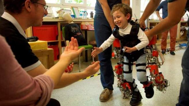 Álvaro, afectado por atrofia muscular espinal, camina hacia sus padres durante una prueba del exoesqueleto.