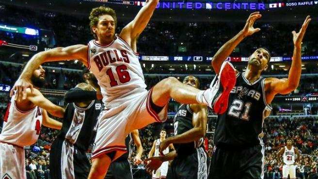 El pívot español Pau Gasol lucha por un rebote con Tim Duncan en el Bulls - Spurs.