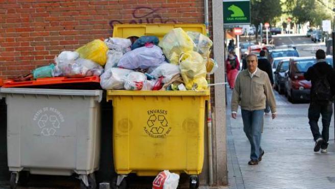 Un cubo lleno de bolsas de basura en una calle de Madrid.