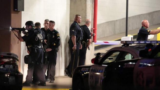 Varios policías se protegen, en un aparcamiento de Dallas (EE UU), de un tiroteo en el que han muerto al menos cinco agentes por los disparos de varios francotiradores.