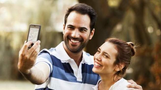 Una pareja se hace un 'selfie' con un teléfono móvil.