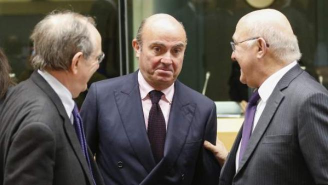El ministro español en funciones de Economía Luis de Guindos (c) conversa con el ministro italiano de Finanzas Pier Carlo Padoan (i) y su homólogo francés Michel Sapin (i) durante el encuentro del Eurogrupo celebrado en Bruselas.