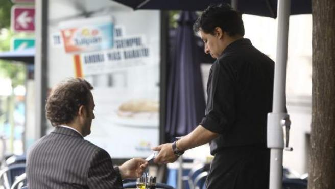Un camarero atiende a un cliente en una terraza.
