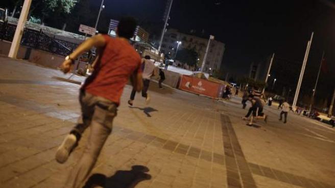 Varias personas corren y se esconden como del ejército turco en la plaza Taksim, en Estambul.