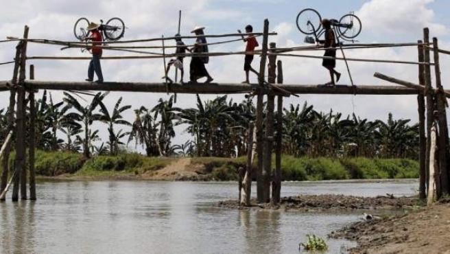 Filipinos cruzan un río en Mamasapano en la provincia de Maguindanao al sur de Filipinas, la zona del país en la que se mantiene vivo el conflicto.