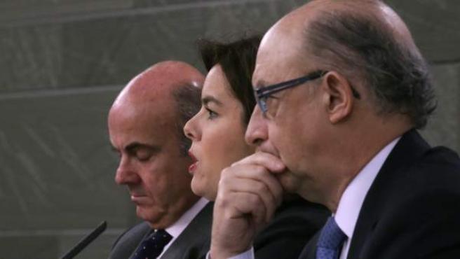 La vicepresidenta del Gobierno, Soraya Sáenz de Santamaría, acompañada por Luis de Guindos (i) y Cristóbal Montoro, mientras explican la Actualización del Programa de Estabilidad 2016-2019.