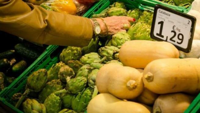 Una mujer compra vegetales en un supermercado.