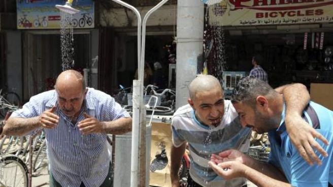 Varios ciudadanos de Bagdad se refrescan ante las altas temperaturas registradas en la capital de Irak.
