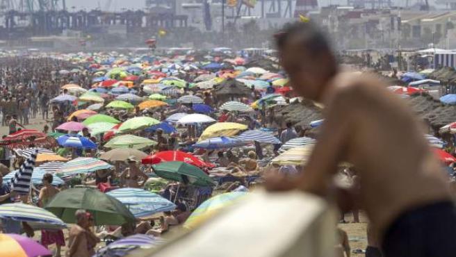 Un hombre observa la playa de la Malvarrosa abarrotada por miles de bañistas.