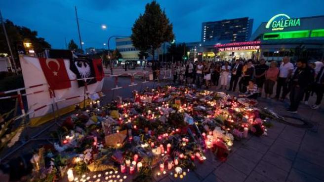 Flores y velas encendidas frente al centro comercial Olympia de Múnich, escenario del tiroteo mortal.