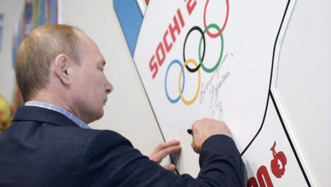 El presidente ruso Vladimir Putin estampa su firma en una pared durante su visita a un centro de entrenamiento para voluntarios de los Juegos Olímpicos de Invierno de Sochi, Rusia.