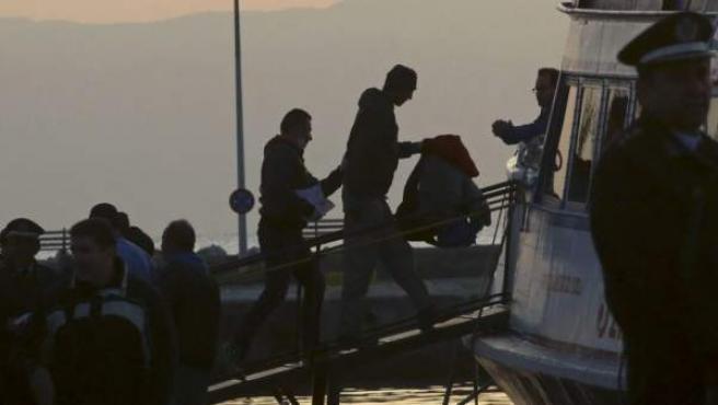 Dos migrantes suben a uno de los barcos que les llevará desde la isla de Lesbos a Turquía.