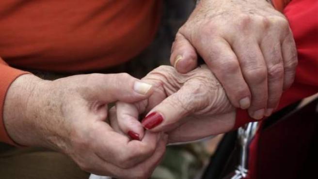 Una pareja de ancianos se da la mano.