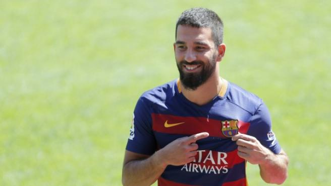 El centrocampista turco Arda Turan señala el escudo del Fútbol Club Barcelona de su camiseta durante su presentación como nuevo jugador de la entidad.