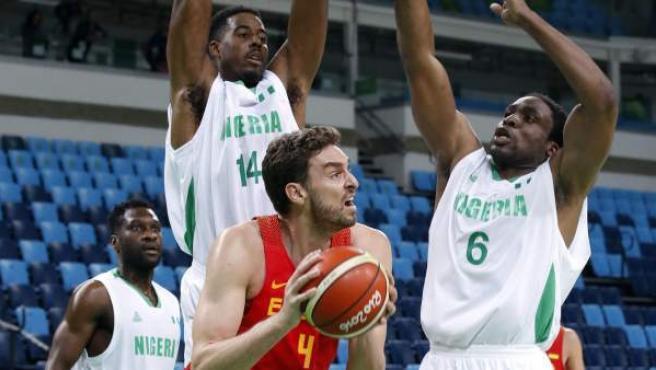 Pau Gasol (c) de España ante Alade Aminu (i) y Ikechukwu Diogu (d) de Nigeria .