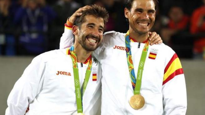 Los tenistas españoles Rafael Nadal y Marc López celebran la medalla de oro ganada en la final de tenis de dobles masculino