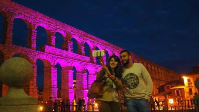 Una pareja se hace un 'selfie' ante el Acueducto de Segovia iluminado.