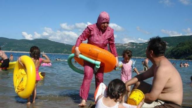 Una mujer usa un burkini en la costa.