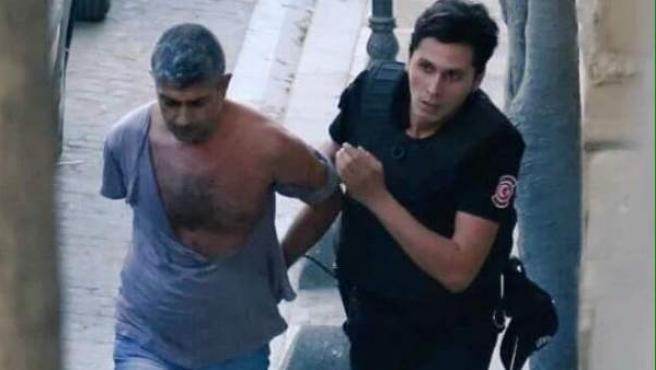 Un policía turco se lleva detenido al caricaturista español Dogan Güzel.