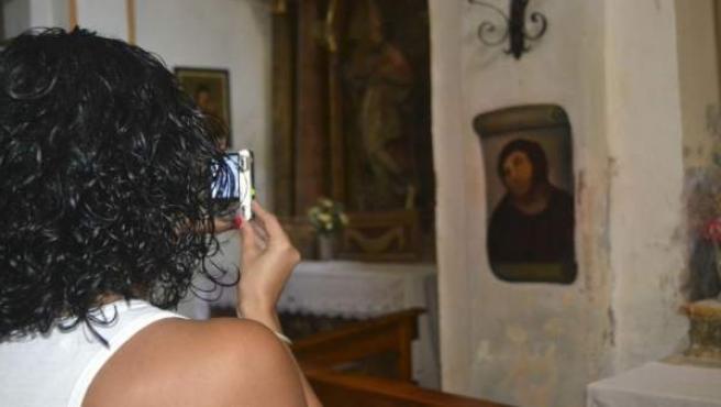 Una mujer realiza una fotografía de la pintura del Ecce homo del Santuario de la Misericordia de Borja (Zaragoza).