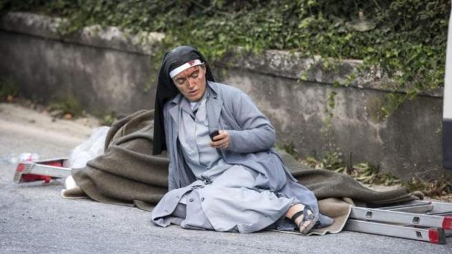 Una monja revisa su teléfono móvil al lado de una víctima tumbado en una escalera después del terremoto en Amatrice, Italia.