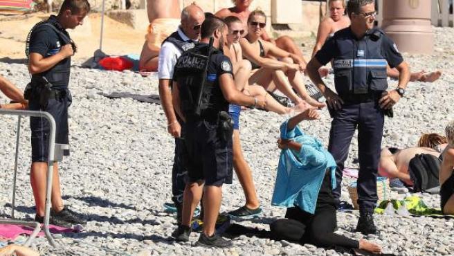 Cuatro agentes de la policía francesa rodean a una musulmana en una playa de Niza y le obligan a quitarse el velo.
