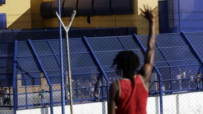 Una persona saluda a los internos en el Centro de Internamiento de Extranjeros (CIE) de Aluche.