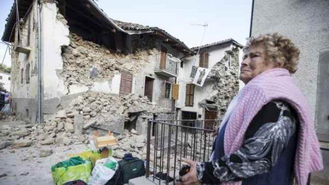Una mujer espera junto a los escombros en Accumoli, en el centro de Italia, destruido por el terremoto.