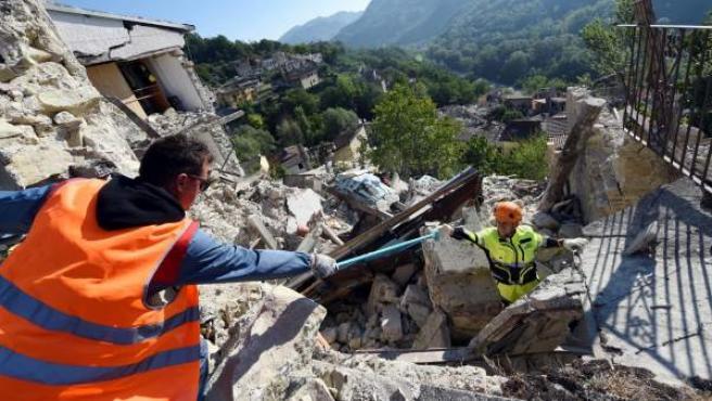 Los miembros de los servicios de rescate trabajan en la búsqueda de supervivientes entre los escombros en Pescara del Tronto.