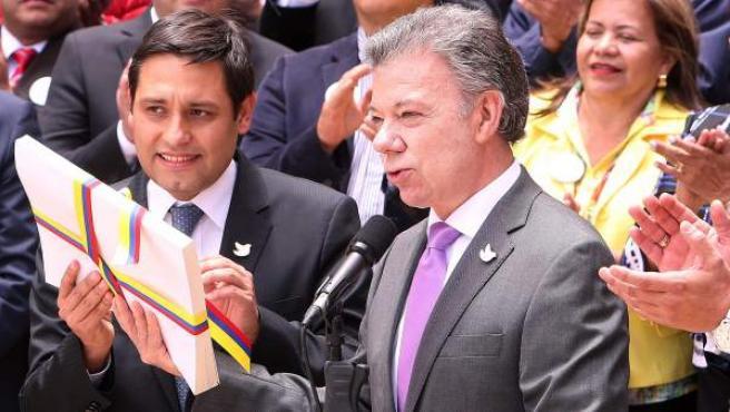 El presidente de Colombia, Juan Manuel Santos, entrega al presidente del Congreso de Colombia, Mauricio Lizcano, el texto definitivo del acuerdo de paz con la guerrilla de las FARC en Bogotá.