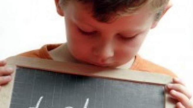 Un niño sostiene una pizarra donde se puede leer 'dislexia'.