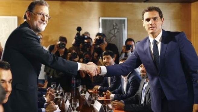 El jefe del Gobierno, Mariano Rajoy y el líder de Ciudadanos, Albert Rivera, se estrechan la mano durante la reunión de sus respectivas delegaciones en la que van a certificar el acuerdo de investidura.