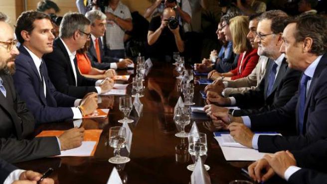El jefe del Gobierno, Mariano Rajoy, y el líder de Ciudadanos, Albert Rivera, durante la reunión de sus respectivas delegaciones en la que van a certificar el acuerdo de investidura.