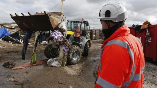 Uno de los trabajadores utiliza una excavadora para tirar las tiendas y casas de madera (con palés) de la parte sur de la jungla de Calais.