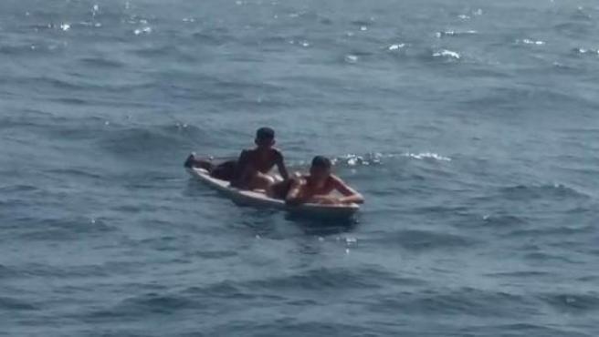 Dos inmigrantes en una tabla de surf