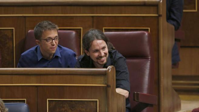 El secretario general de Podemos,Pablo Iglesias (d), y el portavoz de Podemos en el Congreso Iñigo Errejón (i) siguen desde sus escaños la intervención de l presidente del gobierno en funciones Mariano Rajoy, en la primera jornada del debate de investidura al que se somete.