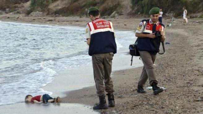 Un policía recoge el cadáver del niño sirio Aylan de una playa de Turquía.