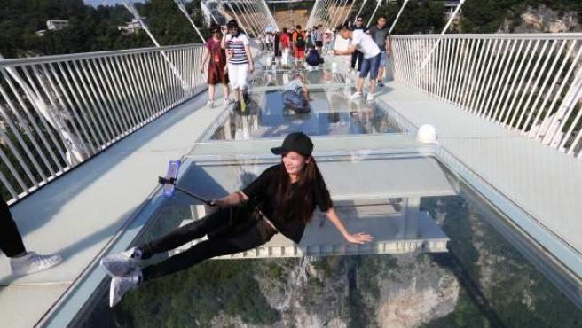 Una turista se hace un selfie en el puente de cristal más largo del mundo, en China.