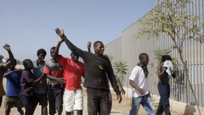 Algunos de los más de 100 'sin papeles' que han logrado asaltar la valla de Melilla este domingo.