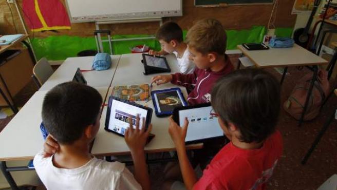 Niños utilizando su tableta para clase en un colegio.