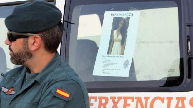 Un efectivo de la Guardia Civil junto al cartel de Diana Quer, al inicio de la primera batida ciudadana organizada por el ayuntamiento de la localidad para tratar de dar con algún indicio de la joven.