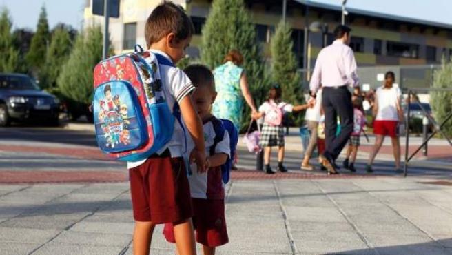 Niños a la entrada del colegio con uniformes escolares.