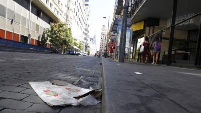 Cartones, colillas, restos de papel y manchas en la acera en la calle Jacometrezo.