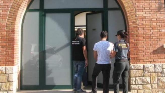 Uno de los detenidos por agredir presuntamente a los músicos entra en el cuartel escoltado por dos guardias civiles.