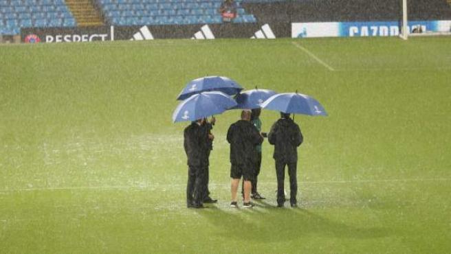 Lluvia en el Etihad Stadium antes del partido entre Manchester City y el Borussia Mönchengladbach con los árbitros examinando el césped.