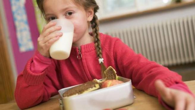 Una niña comiendo en el colegio.