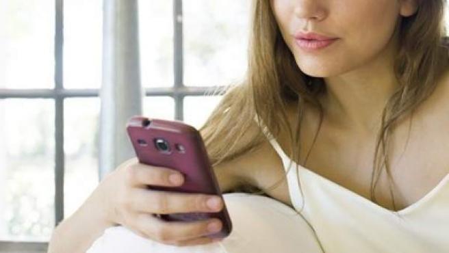 Una mujer consulta su teléfono móvil.
